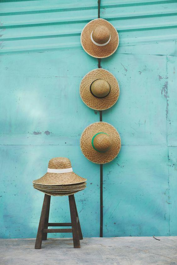beach hats on aqua wall